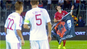 Serbia's Stefan Mitrovic (#13) retrieving the Albanian flag with Albania captain Lorik Cana (#5) and Amir Abrashi (#22) looking on (Source: espnfc.com)