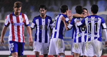 Real Sociedad players celebrating while Atletico Madrid's Cristian Ansaldi (#15) walking on dejected. (Source: bbc.co.uk)