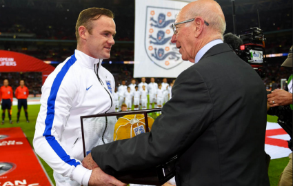 Wayne Rooney (Left) being given the golden cap by Sir Bobby Charlton before the Slovenia match. (Source: mirror.co.uk)