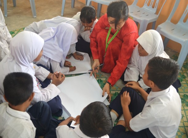 Cikgu Ashley helping the students make the butcher paper into a four-piece, eight-page book while talking them through the process.